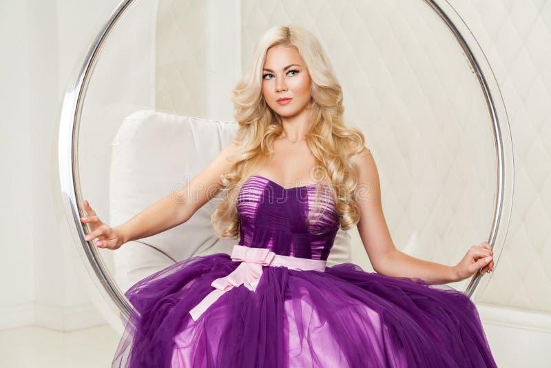 Porträt der attraktiven blonden Eleganzfrau im modernen purpurroten Kleid mit dem Make-up und langer gewellter Frisur, die in geh stockbild