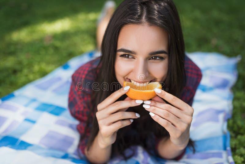 Porträt der attraktiven brunette Frau, die auf grünem Gras im Freien in der orange Frucht Essens, Kopienraum für Ihre Werbebotsch stockfotografie