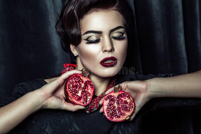 Porträt der attraktiven Frau mit dem hellen Glättungsmake-up, das in der Hand Granatäpfel auf dunklem Studiohintergrund hält stockbilder
