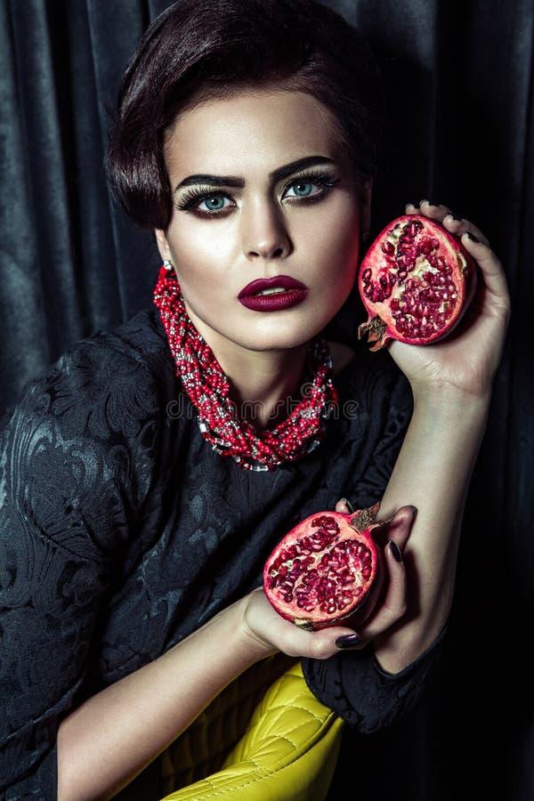 Porträt der attraktiven Frau mit dem hellen Glättungsmake-up, das in der Hand Granatäpfel hält und Kamera auf dunklem Studio betr lizenzfreie stockbilder