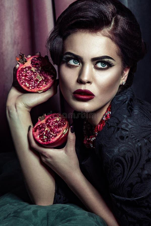 Porträt der attraktiven Frau mit dem hellen Glättungsmake-up, das in der Hand Granatäpfel hält und oben auf dunklem Studiohinterg stockfoto