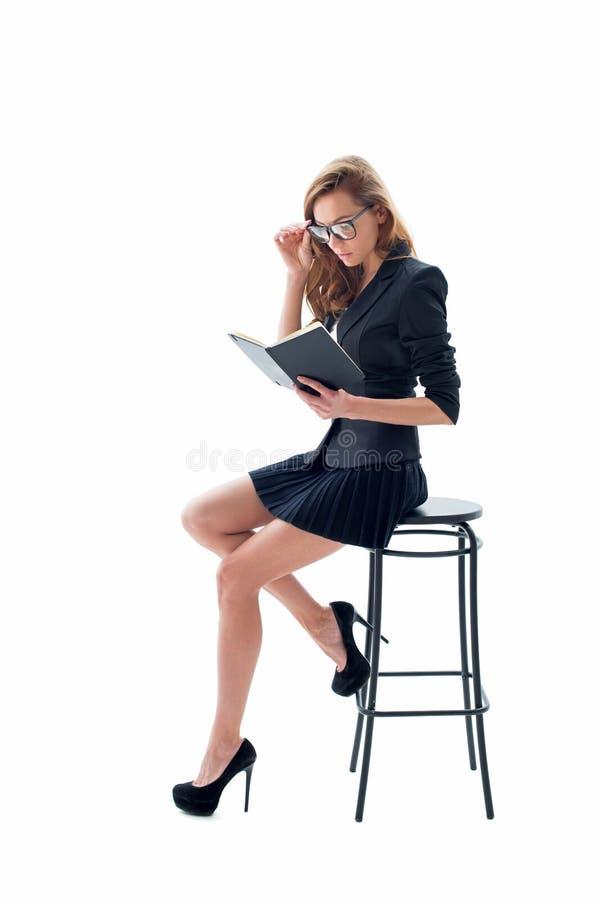 Porträt der attraktiven Frau mit den Gläsern und Notizbuch, die auf einem Stuhl sitzen lizenzfreie stockbilder