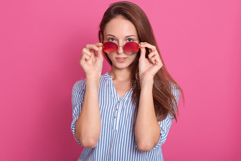 Porträt der attraktiven Frau der Mode, die über Sonnenbrille späht Weibliches Modell, das gegen rosa Studiohintergrund, Tragen st lizenzfreie stockfotografie