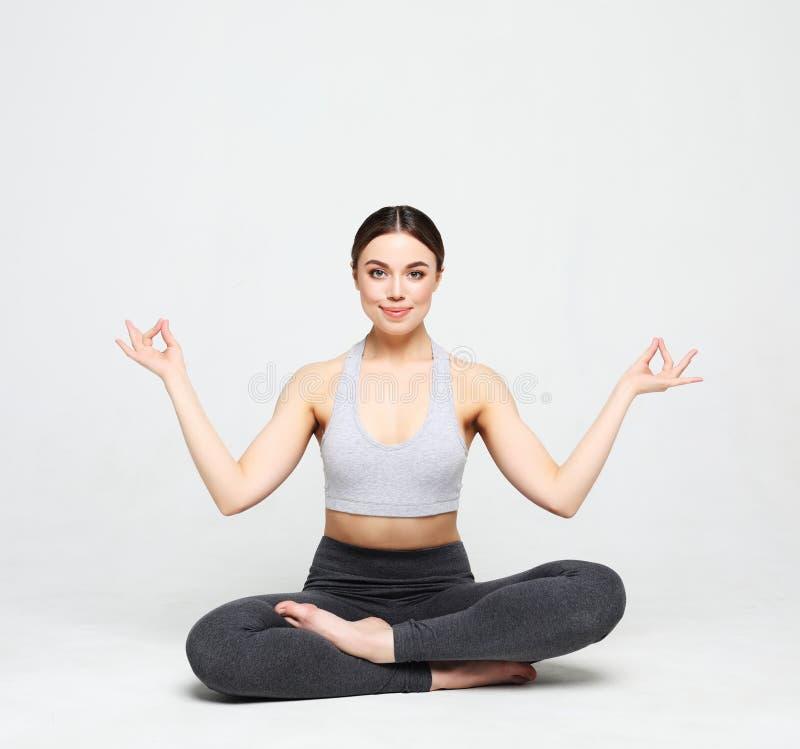 Porträt der attraktiven Frau Yoga, pilates tuend über hellgrauem Hintergrund Gesunder Lebensstil und Sportkonzept stockbilder