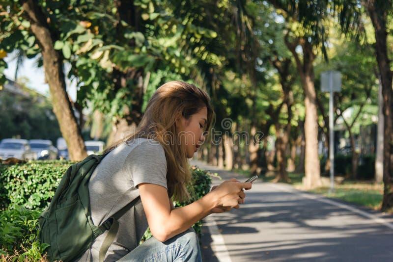 Porträt der attraktiven glücklichen asiatischen Frau, die Smartphone beim Sitzen auf Straßenrand an der Stadtstraße hält lizenzfreie stockbilder