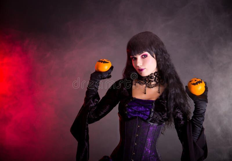 Porträt der attraktiven Hexe in purpurrotem gotischem Halloween-Kostüm lizenzfreies stockfoto