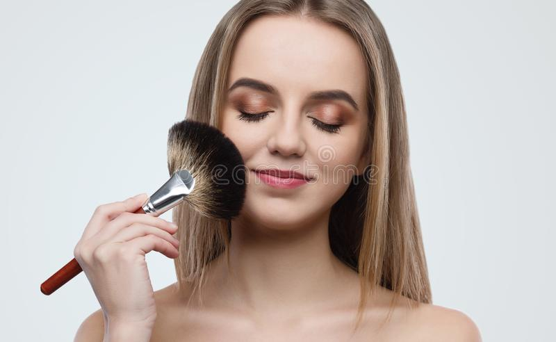 Porträt der attraktiven Holdingbürste der jungen Frau stockfotografie