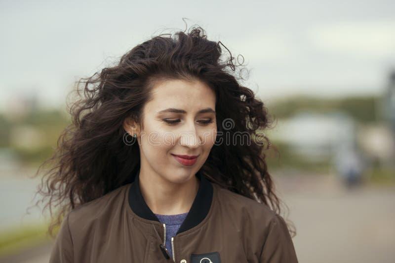 Porträt der attraktiven jungen Brunettefrau mit dem langen gelockten Haar lizenzfreies stockfoto