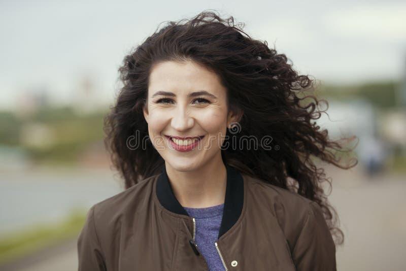 Porträt der attraktiven jungen Brunettefrau mit dem langen gelockten Haar stockbild