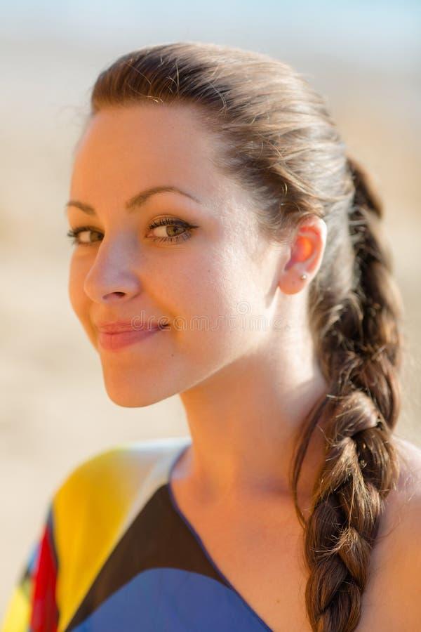 Porträt der attraktiven jungen Frau, die das Kameralächeln betrachtet lizenzfreie stockbilder