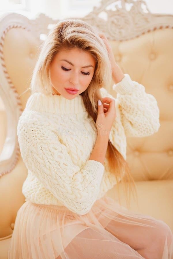 Porträt der attraktiven jungen Frau, die in einem Stuhl sitzt Schönes Mädchen schaut unten, Hände im Haar lizenzfreie stockfotos