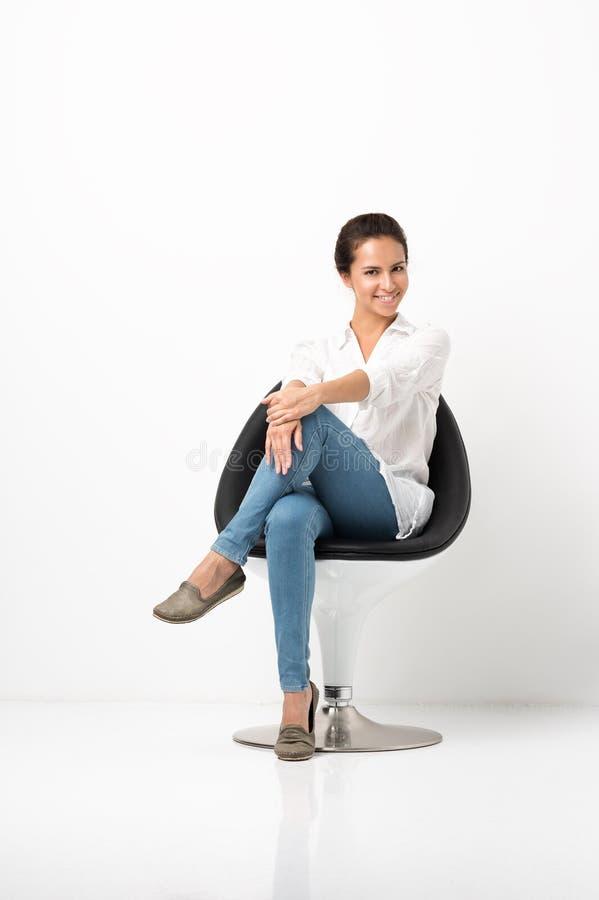 Porträt der attraktiven jungen Frau, die in einem Stuhl sitzt Weißes Hemd und Jeans lizenzfreies stockbild