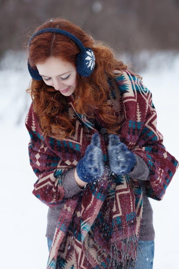 Porträt der attraktiven jungen gelockten rothaarigen Frau in den blauen Handschuhen und in den Kopfhörern lizenzfreies stockbild