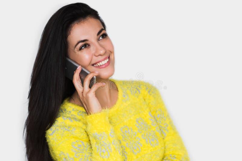 Porträt der attraktiven jungen glücklichen Frau mit intelligentem Telefon, tragende gelbe Strickjacke, mit recht toothy Lächeln,  stockfotografie