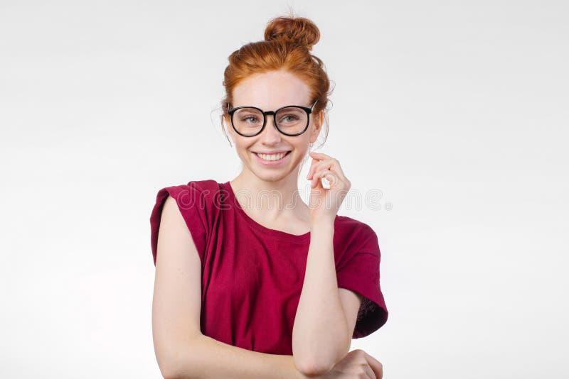 Porträt der attraktiven jungen Rothaarigefrau, die mit Gläsern lächelt lizenzfreie stockbilder