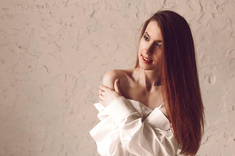 Porträt der attraktiven jungen Rothaarigefrau mit dem langen Haar, das im Herrenhemd sitzt lizenzfreies stockbild