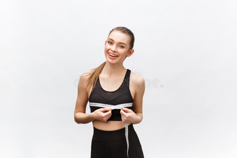 Porträt der attraktiven kaukasischen lächelnden Frau mit dem messenden Band lokalisiert auf weißem Hintergrund lizenzfreies stockfoto