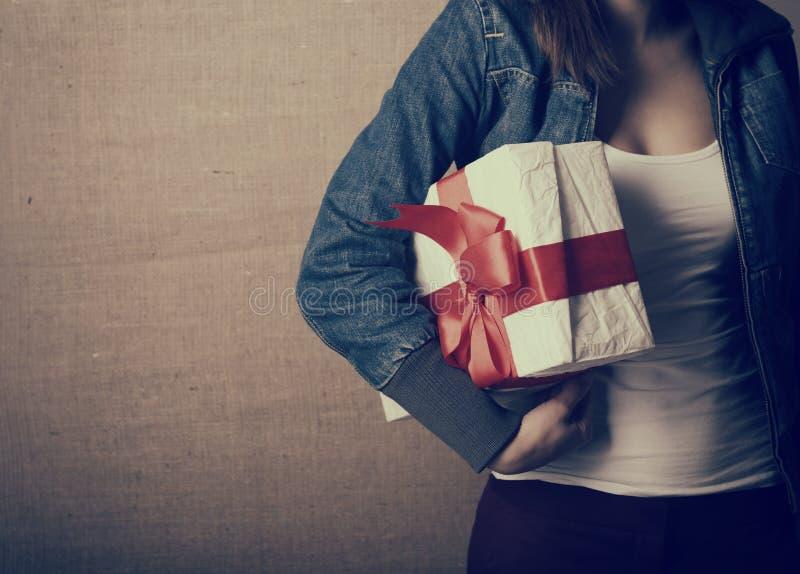Porträt der attraktiven netten Mädchenholdinggeschenkbox mit rotem b lizenzfreie stockbilder