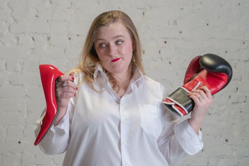 Porträt der attraktiven Plusgrößenfrau, welche die Gefühle der Wahl lokalisiert über weißem Hintergrund hat Ein Mädchen in einem  stockfoto