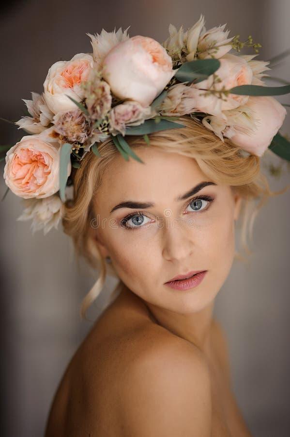 Porträt der attraktiven schulterfreien Blondine in einem zarten Blumenkranz stockfotografie