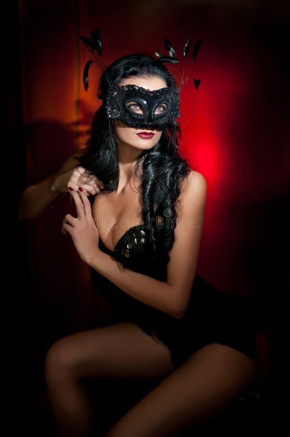 Porträt der attraktiven sinnlichen jungen Frau mit Maske, zuhause Sinnliche Brunettedame, die provozierend auf rotem Hintergrund  stockfotografie