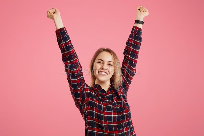 Porträt der aufgeregten frohen frohen Frau hebt Hände, feiert großen Erfolg, ausdrückt ihr Glück, glaubt, um Sieger, reciev zu se stockfotos