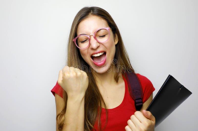 Porträt der aufgeregten lächelnden Studentin, die Erfolg lokalisiert über weißem Hintergrund feiert lizenzfreie stockfotografie