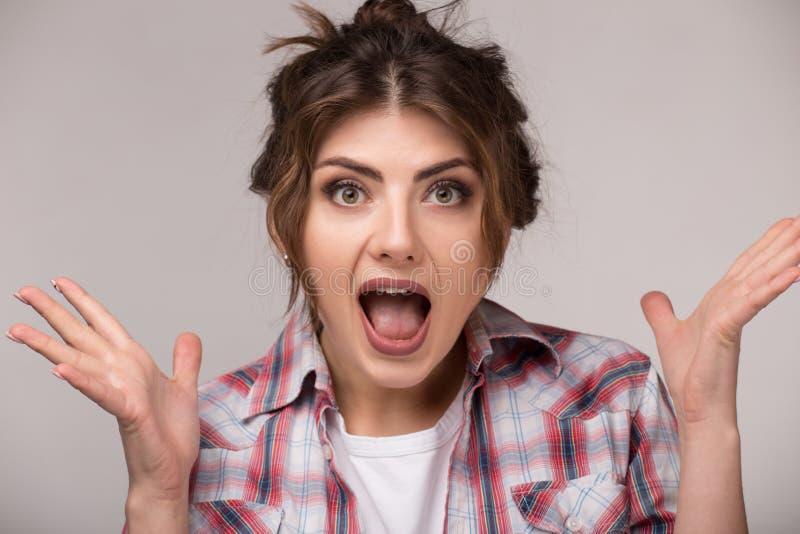 Porträt der aufgeregten schreienden jungen Frau mit Handgeste stockbilder