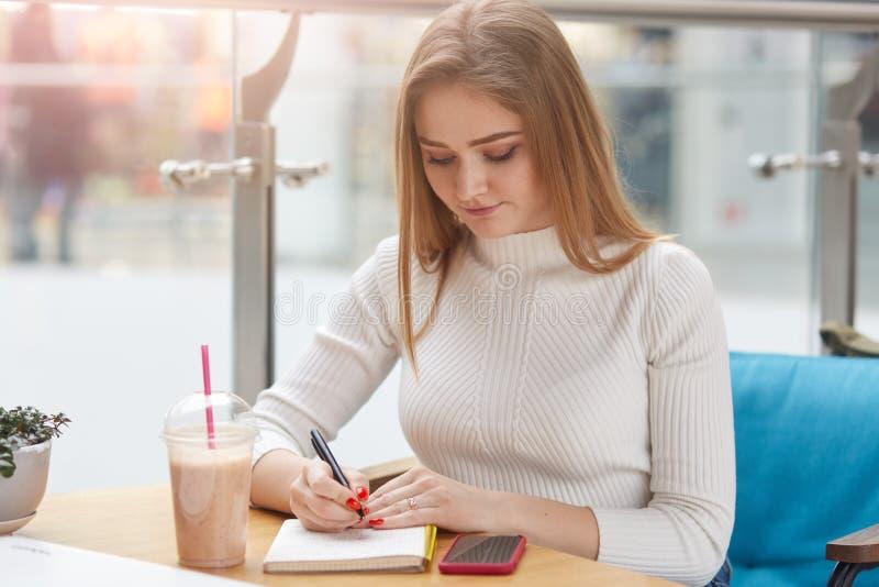 Porträt der aufmerksamen ehrgeizigen jungen Frau, die bei Tisch, Punkte in ihren täglichen Planer schreibend sitzt und machen Ken lizenzfreie stockbilder