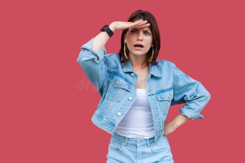 Porträt der aufmerksamen schönen brunette jungen Frau mit Make-up in der Stellung der zufälligen Art des Denims ernsthaft, Hand a lizenzfreie stockfotografie