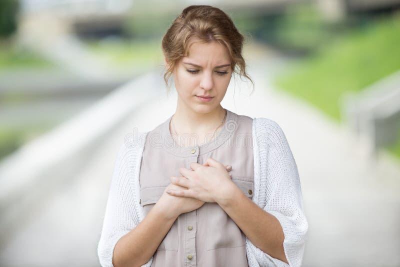 Porträt der betonten oder einsamen Frau mit Herzen schmerzen draußen lizenzfreie stockfotografie
