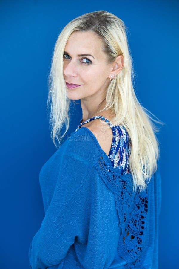 Porträt der blonden Frau in der blauen Strickjacke stockfoto