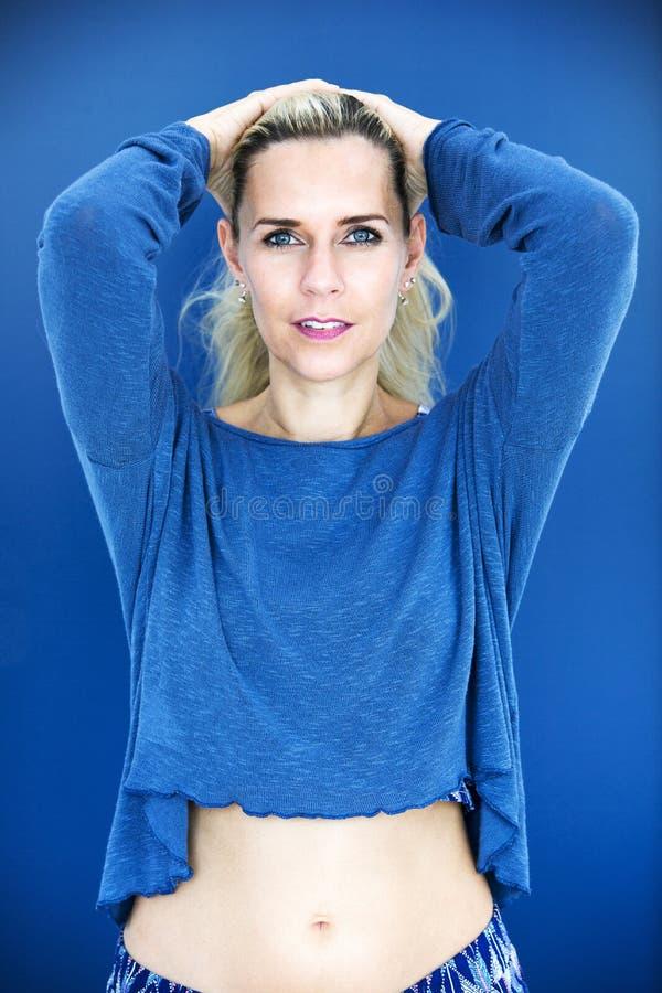 Porträt der blonden Frau in der blauen Strickjacke lizenzfreies stockbild