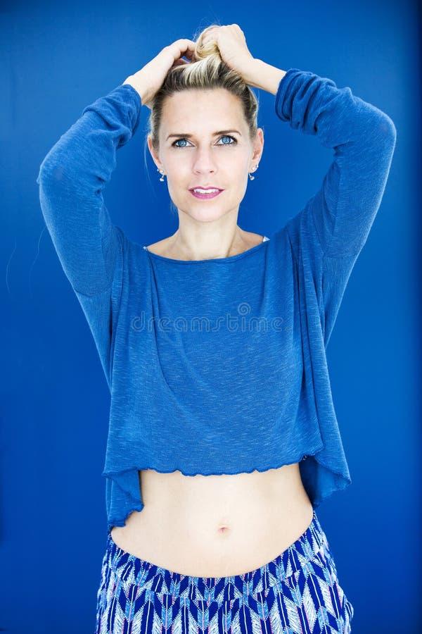 Porträt der blonden Frau in der blauen Strickjacke lizenzfreie stockfotos