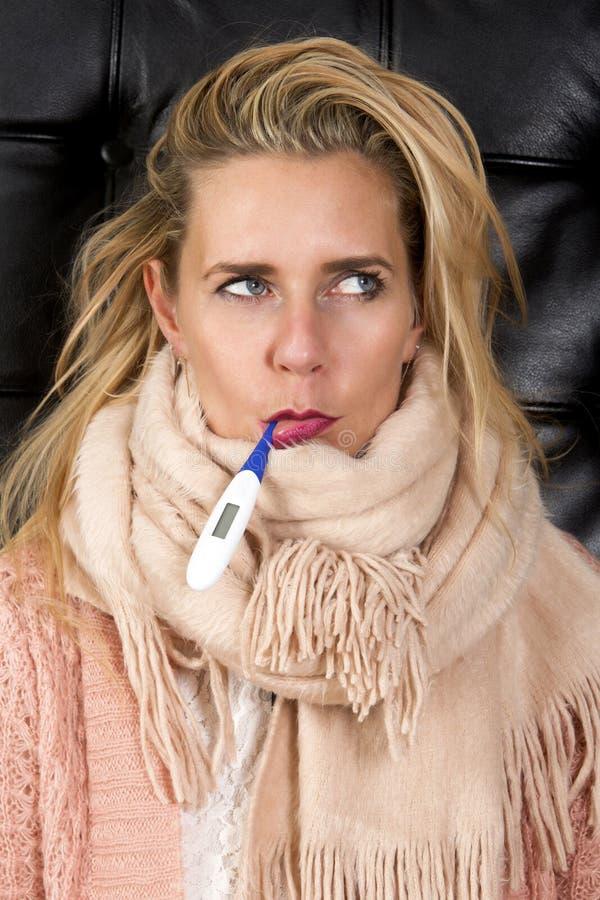Porträt der blonden Frau mit Thermometer lizenzfreie stockfotografie