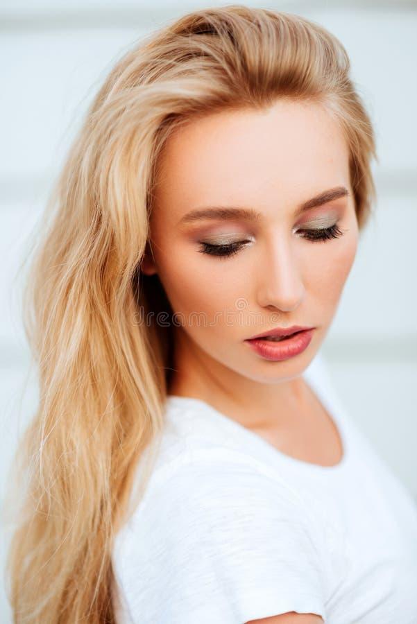 Porträt der blonden jungen Frau, die draußen aufwirft stockfotos