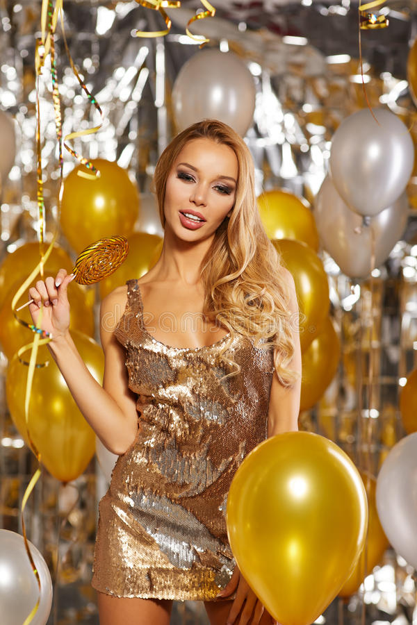Porträt der blonden jungen Frau zwischen goldenen Ballonen und Band lizenzfreies stockbild