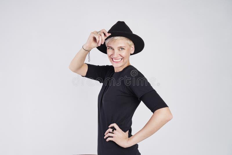 Porträt der blonden kaukasischen Frau, die schwarze Kleidung und den Hut lächelt und aufwirft auf weißem Hintergrund trägt stockbilder