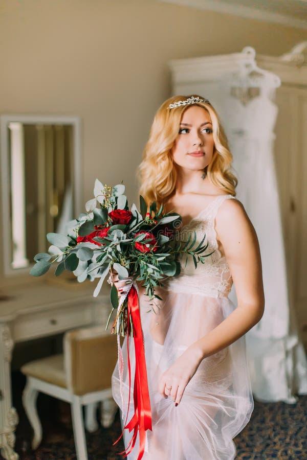 Porträt der blonden sexy Braut in der weißen Unterwäsche mit Blumenstrauß Luxuriöser Wohnungshintergrund lizenzfreie stockfotografie