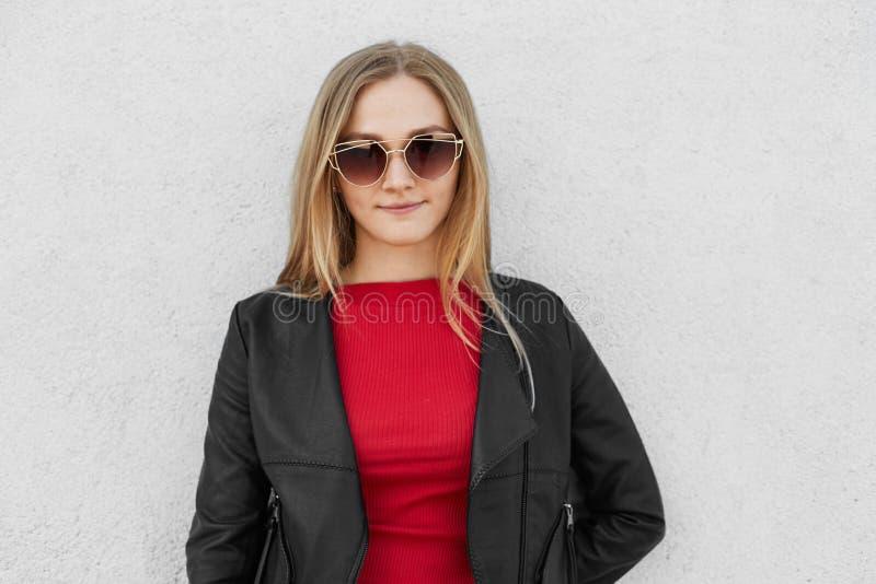 Porträt der blonden weiblichen tragenden Sonnenbrille, der roten Strickjacke und schwarzen der Lederjacke, die gegen weiße Betonm stockfotos