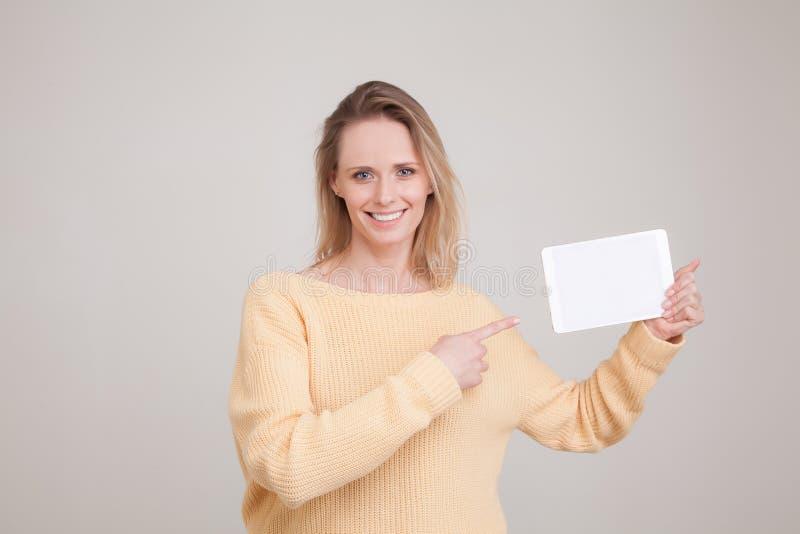 Porträt der Blondineholdingtablette in ihren Händen und im Lächeln, die Kamera betrachtend und zeigen auf die Tablette mit ihrem  stockbild