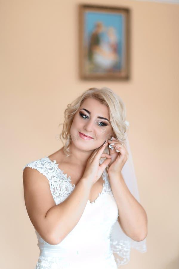 Porträt der Braut als tragende Ohrringe in einem weißen Heiratskleid Schönheit und Schmuckkonzept stockfoto
