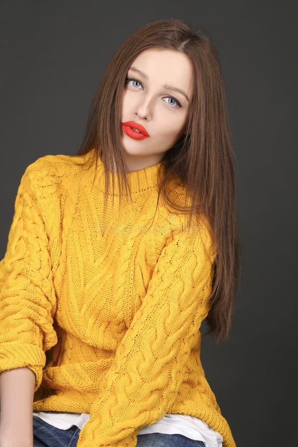 Porträt der Brunettefrau in der gelben Jacke mit den roten Lippen lizenzfreies stockbild
