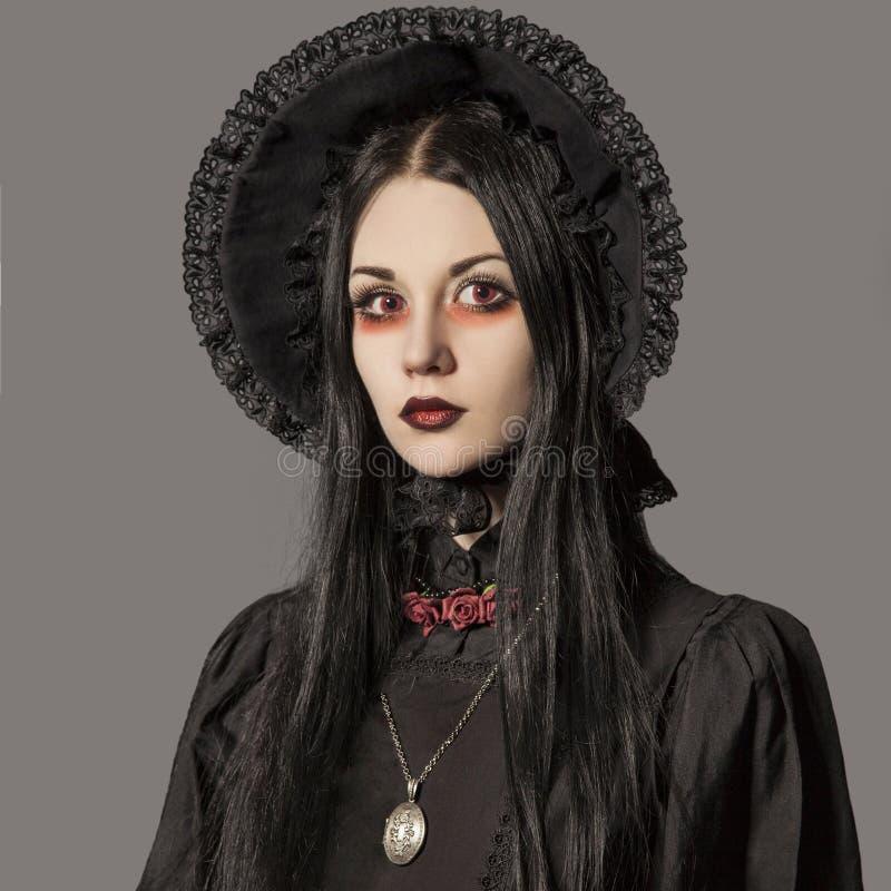 Porträt der Brunettefrau im schwarzen Kleid und im klassischen gotischen Schweinestall stockfotos