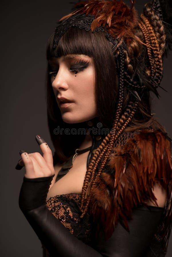 Porträt der Brunettefrau mit dunklem gotischem Make-up und kreativer Frisur stockbilder