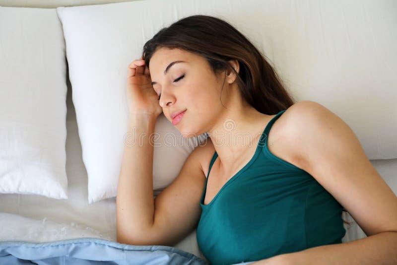 Porträt der Brunettefrau zu Hause schlafend im Bett auf Kissen lizenzfreie stockbilder