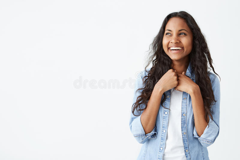 Porträt der charismatischen und reizend afro-amerikanischen Frau mit dem langen gewellten Haar, das stilvolles Denimhemd, lächeln lizenzfreie stockfotografie