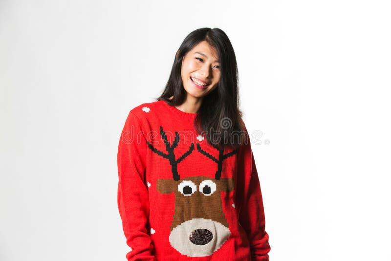 Porträt der Chinesin in der Weihnachtsstrickjacke, die vor grauem Hintergrund steht stockfotos