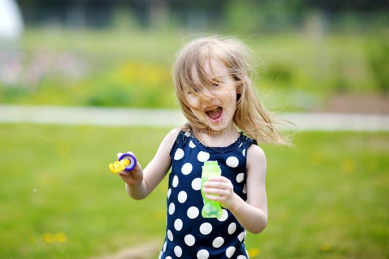 Porträt der durchbrennenSeifenblasen des kleinen Mädchens stockfotografie