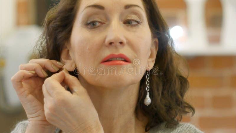 Porträt der eleganten Frau versucht an einen Ohrring und einen Blick am Spiegel lizenzfreie stockfotos